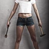 拿着锤子和板钳扳手的性感的女孩 免版税库存图片