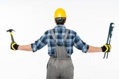 拿着锤子和管扳手的工作员 库存照片