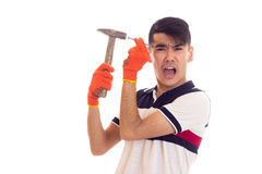 拿着锤子和钉子的橙色手套的人 库存照片