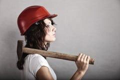 拿着锤子工具的安全帽的性感的女孩 库存照片