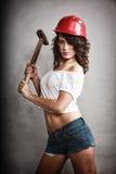 拿着锤子工具的安全帽的性感的女孩 免版税库存照片