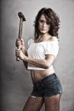 拿着锤子工具的性感的女孩安装工 库存照片