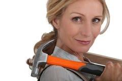 拿着锤子的白肤金发的妇女 免版税库存图片
