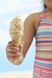 拿着锥体冰淇凌的女孩 免版税库存图片