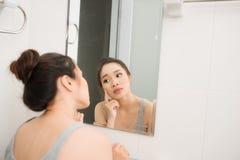 拿着镜子,接触和担心她的面孔的亚裔妇女 库存照片