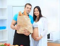 拿着长方形宝石的包裹丈夫和怀孕的妻子 库存照片
