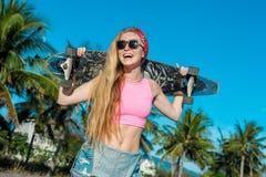 拿着长的委员会的年轻微笑的妇女画象在海滩的棕榈附近 免版税图库摄影