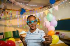 拿着闪烁发光物和杯形蛋糕的逗人喜爱的男孩在生日聚会期间 库存图片