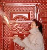 拿着闪烁发光物烟花用手的亚裔中国女孩在前边红色门  浅黑肤色的男人,看 免版税库存图片