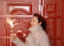 拿着闪烁发光物烟花用手的亚裔中国女孩在前边红色门  浅黑肤色的男人,看 免版税库存照片