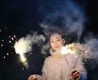 拿着闪烁发光物烟花用手的亚裔中国女孩在黑背景 浅黑肤色的男人,看 免版税库存图片