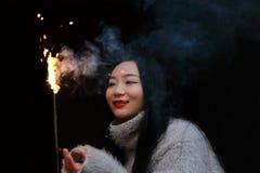 拿着闪烁发光物烟花用手的亚裔中国女孩在黑背景 浅黑肤色的男人,看 库存图片