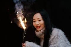 拿着闪烁发光物烟花用手的亚裔中国女孩在黑背景 浅黑肤色的男人,看 免版税图库摄影