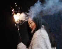 拿着闪烁发光物烟花用手的亚裔中国女孩 浅黑肤色的男人,看 免版税库存照片
