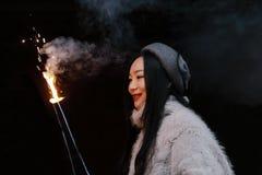 拿着闪烁发光物烟花用手的亚裔中国女孩 浅黑肤色的男人,看 免版税图库摄影