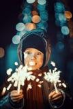 拿着闪烁发光物的一个逗人喜爱的小男孩的画象 免版税库存图片