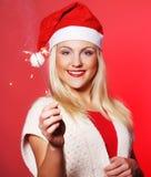 拿着闪烁发光物的圣诞老人帽子的女孩 免版税库存照片