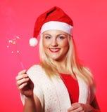 拿着闪烁发光物的圣诞老人帽子的女孩 图库摄影