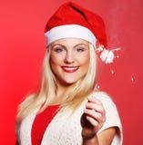 拿着闪烁发光物的圣诞老人帽子的女孩 库存照片