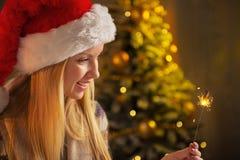 拿着闪烁发光物的圣诞老人帽子的少年女孩 免版税库存图片