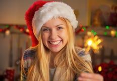 拿着闪烁发光物的圣诞老人帽子的少年女孩 库存图片