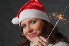 拿着闪烁发光物的圣诞老人帽子的逗人喜爱的女孩 免版税库存照片
