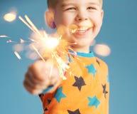 拿着闪烁发光物的小男孩 免版税库存照片