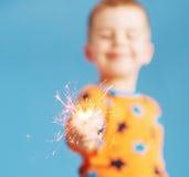 拿着闪烁发光物的男孩被弄脏的画象 免版税库存图片