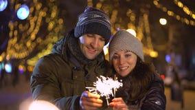 拿着闪烁发光物的逗人喜爱的年轻夫妇 影视素材