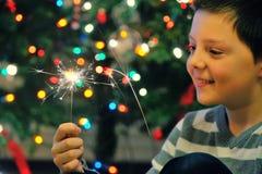拿着闪烁发光物的年轻男孩 免版税库存图片