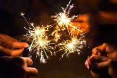 拿着闪烁发光物,明亮的欢乐圣诞节闪烁发光物的人的手 库存图片