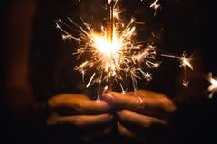 拿着闪烁发光物,明亮的欢乐圣诞节闪烁发光物的妇女 库存照片