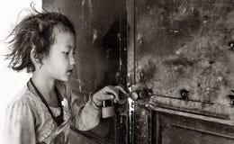 拿着闭合的教室等待的老师的门小女孩打开, Sapa,越南 免版税库存照片