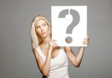 拿着问号标志的白肤金发的女孩 库存图片