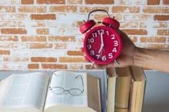 拿着闹钟上面开放书的一个人,读时间 免版税库存图片