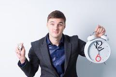 拿着闹钟和手表的年轻商人 图库摄影
