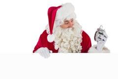 拿着闹钟和标志的愉快的圣诞老人 库存图片