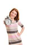 拿着闹钟的微笑的美丽的女孩 免版税库存照片