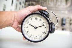 拿着闹钟的手 免版税库存照片