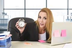 拿着闹钟的担心的可爱的白肤金发的女商人坐在办公桌与计算机膝上型计算机一起使用 库存照片