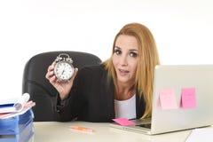 拿着闹钟的担心的可爱的白肤金发的女实业家在运转的办公桌坐膝上型计算机 免版税库存照片