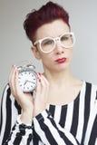 拿着闹钟的红发妇女看起来生气 免版税库存照片
