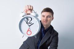 拿着闹钟的年轻商人 免版税库存图片