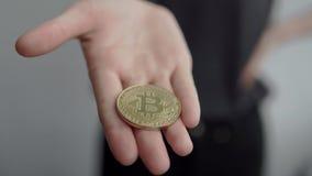 拿着隐藏货币金黄bitcoin的妇女在一只手上铸造并且显示它秘密审议 电子真正金钱 班卓琵琶 影视素材