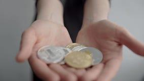 拿着隐藏货币bitcoin ethereum和litecoin硬币在两只手中的妇女和显示它秘密审议 电子 股票视频