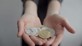 拿着隐藏货币bitcoin ethereum和litecoin硬币在两只手中的妇女和显示它秘密审议 电子 影视素材