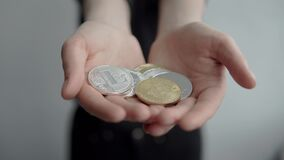 拿着隐藏货币bitcoin ethereum和litecoin硬币在两只手中的妇女和显示它秘密审议 电子 股票录像