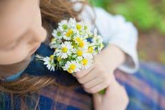 拿着雏菊的花束小女孩在春天 库存图片