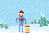 拿着雪撬的圣诞老人帽子的人 平的冬天风景 免版税库存图片