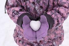 拿着雪球的外套和手套的女孩以心脏的形式 库存图片